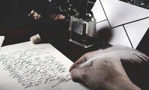 Eine Hand schreibt mit Feder auf ein Blatt Papier.